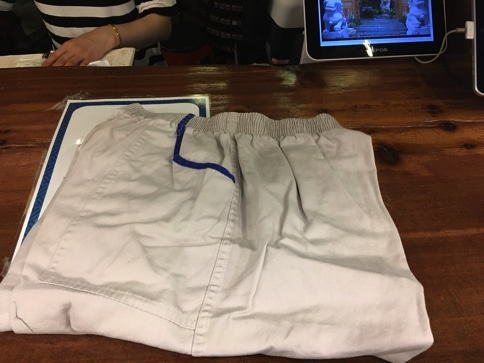 ドラゴンヒルスパのカウンターでダサイ服を受け取とります
